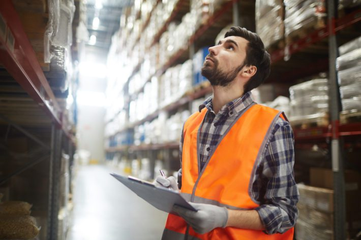 Portrait of warehouse worker looking up the tall shelves doing inventory control