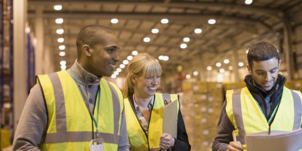 Smiling managers with paperwork in distribution warehouse